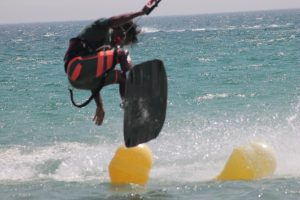 summercamps, young kitesurfer jumping