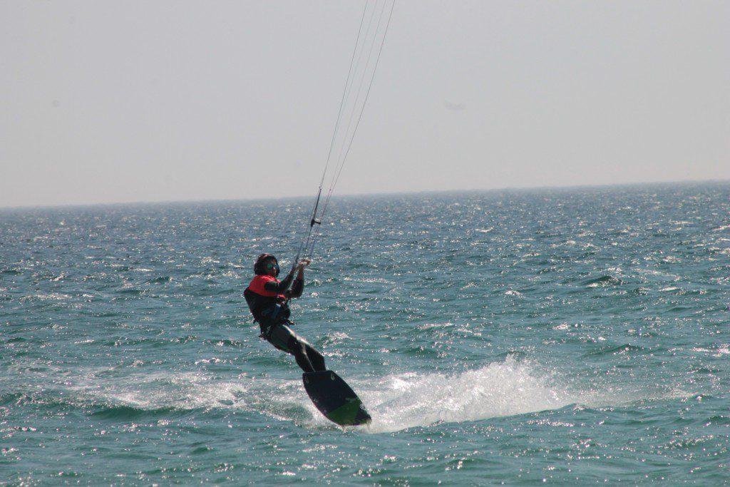 Campamentos juveniles, kitesurfista divirtiendose en Playa Los Lances